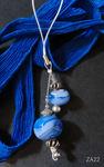 Anhänger mit zwei blau/weißen Perlen an einer Handyschlaufe