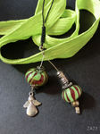 Anhänger mit zwei grün/roten Perlen an einer geflochtenen Handyschlaufe