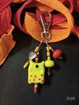 Taschenbaumler mit gelbem Monster und Herzchen-Charm