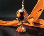 Linse in rot/orange mit schwarzer Katze und blauen Blümchen, unten hängen noch 2 orangene Blümchen