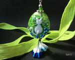 Linse in grün mit weißer Katze und blauen Blümchen, unten hängen noch 2 weiß/blaue Blümchen